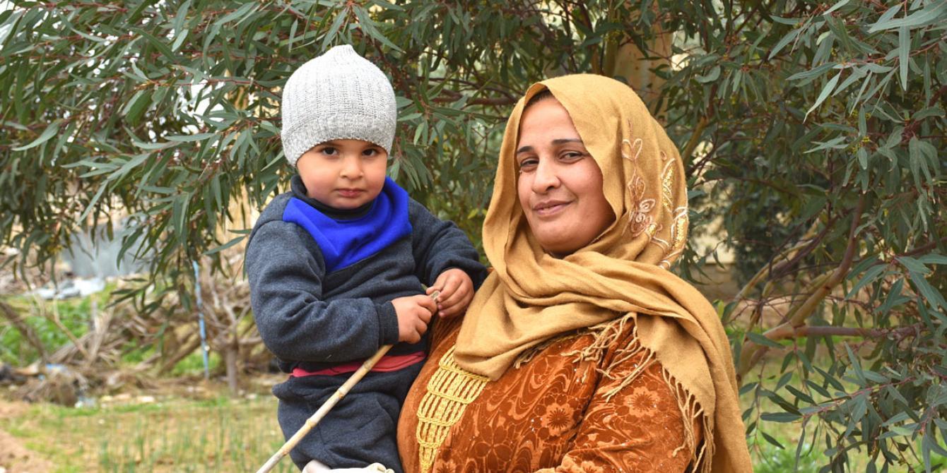خنساء، 34 عاماً، تقف في مزرعة أسرتها في ريف دير الزور، وهي تحمل ابنها.
