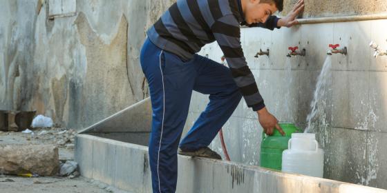 حسن، 15 عاما، أثناء ملء علبتين من بئر عام في أحد أحياء حلب، لتأمين حاجة والدته وأخته من ماء الشرب.