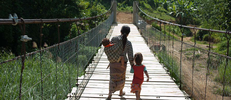 Mother and child walking across the new built suspension bridge in Huameuang. Photo:Tineke D'haese/Oxfam.