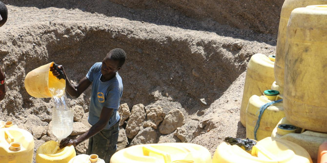 A man scoops water from a water pan in Turkana. Joyce Kabue/Oxfam