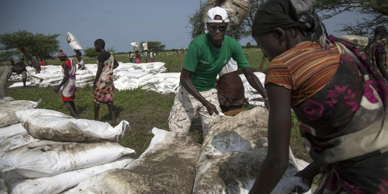 Oxfam staff helps a local staffer carrying sacks of food at a distribution in Pading, South Sudan. Albert González Farran/Oxfam