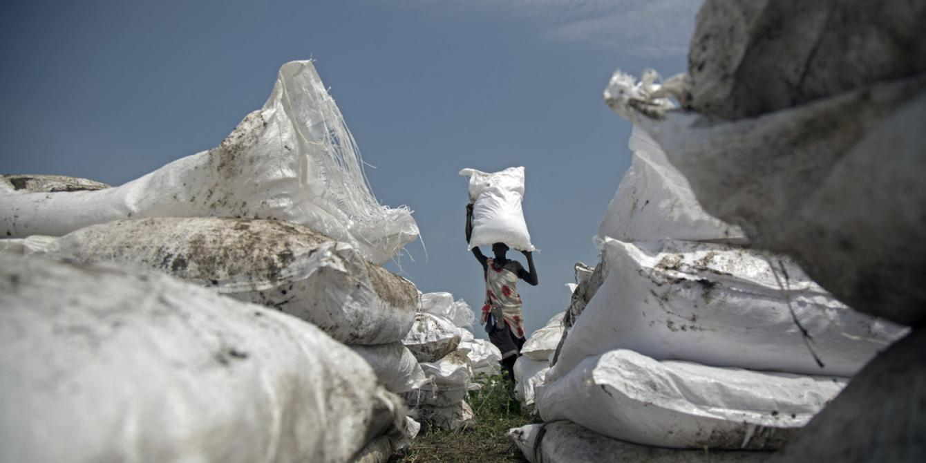 A woman carries a sack of food airdropped by WFP and distributed by Oxfam in Jonglei.