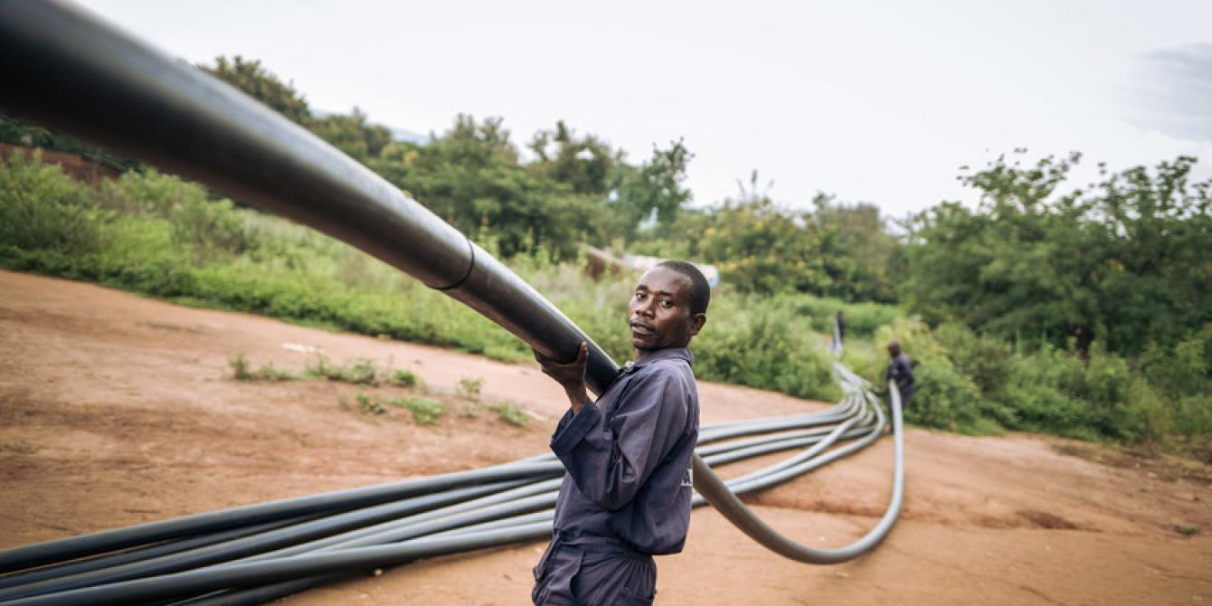 A local engineer carries a plastic pipe used for the water pipeline in Malinde. Alexis Huguet/Oxfam Novib