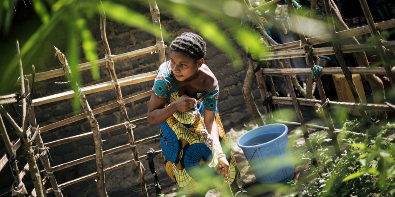 Rebeka Kashidi collects water in a dirty well in Sebele. Alexis Huguet/Oxfam Novib