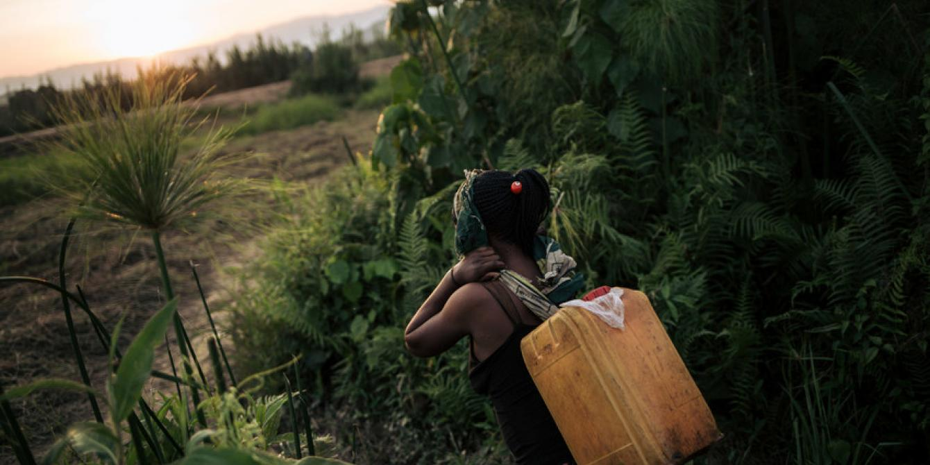 A woman carries water water on the outskirts of Malende. Alexis Huguet/Oxfam Novib