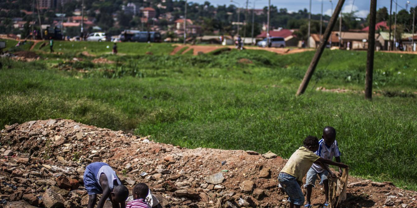 Children play by a dirty stream in one of the low-income settlements in Kampala,Uganda.