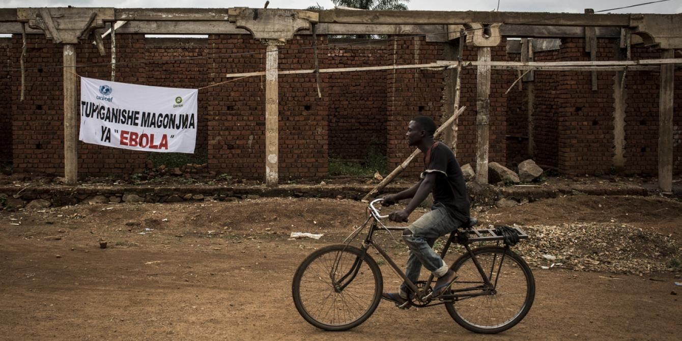 "A Congolese man cycles past a sign saying, ""the fight against Ebola"" in Mangina, DRC. John Wessels/Oxfam"