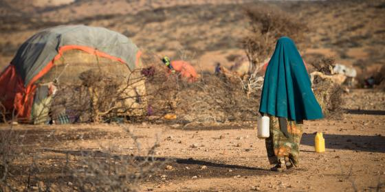 A woman walking through a settlement for displaced people in Somaliland. Allan Gichigi/Oxfam