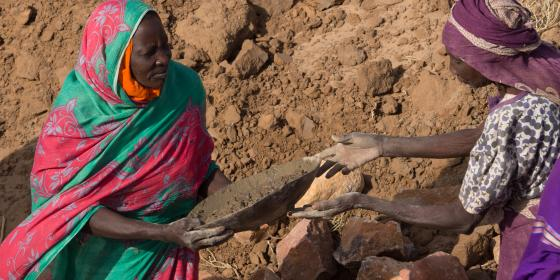 Women transport wet concrete to construct a water reservoir in their village in North Darfur, Sudan.