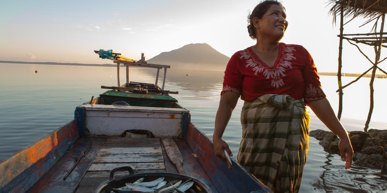 Istri nelayan di Nusa Tenggara Timur menyamabut suami pulang dari laut dengan sekeranjang ikan tangkapan. Credit foto: Rodrigo Ordonez/Oxfam