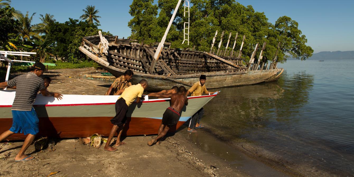 Sekelompok nelayan mendorong perahu baru untuk dicoba di pantai mengikuti petunjuk pemilik perahu Abdul Hamed (depan paling kanan), di Lewoleba, Kecamatan Nubatukan, Kabupaten Lembata, Provinsi Nusa Tenggara Timur, Indonesia. Credit: Rodrigo Ordonez/Oxfam.