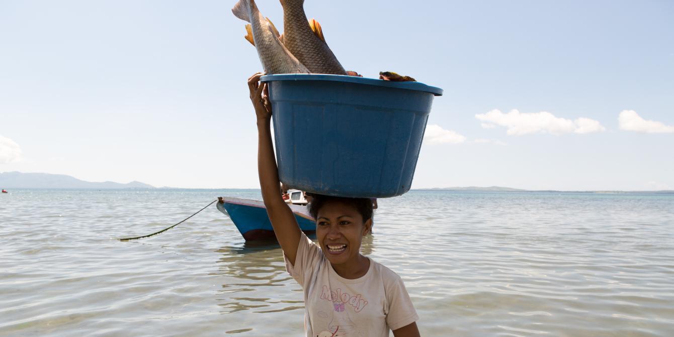 Aisha Selaka, membawa sebakul ikan diatas kepalanya setelah suaminya pulang melaut sejak malam sebelumnya. Aisha dan suaminya tinggal kampung Lewoleba, Nubatukan, Kabupaten Lembata, Provinsi Nusa Tenggara Timur, Indonesia. Credit: Rodrigo Ordonez/Oxfam