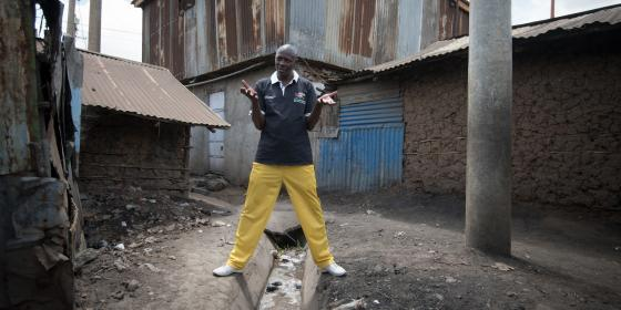 Volunteer Azulu Adeba, 44, describes the poor drainage in his community, where he carries out tax monitoring work with the National Taxpayers Association in Kiambiu, Eastleigh, Nairobi, Kenya. 2016. Photo Credit: Allan Gichigi