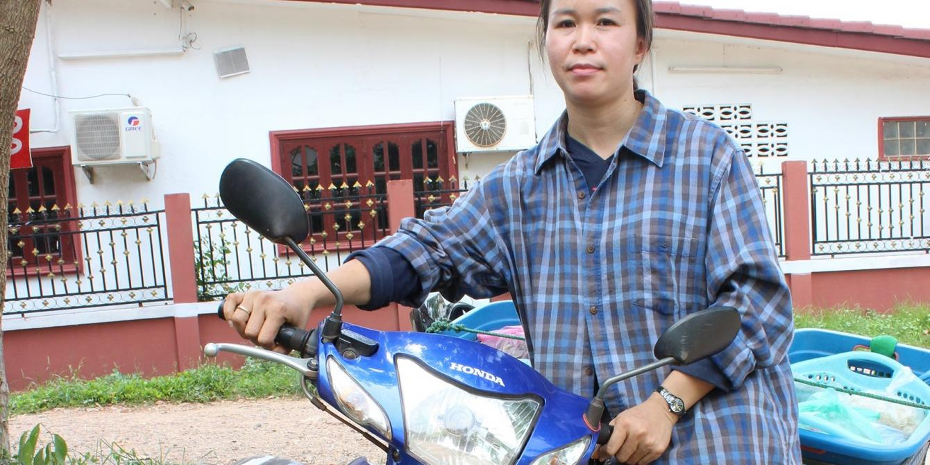 A lao woman standing next to a motorbike she used to deliver food to her customers during the pandemic