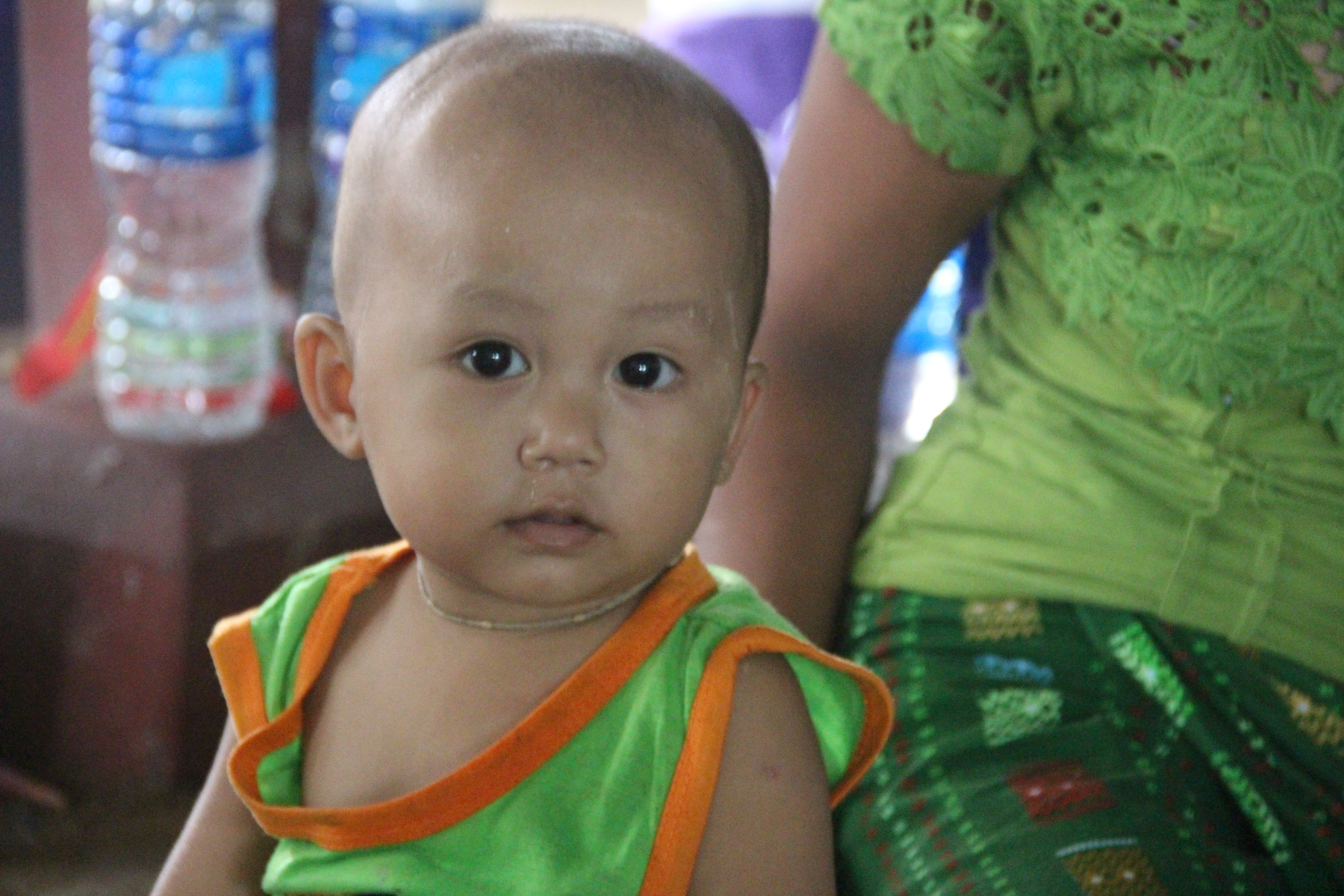 A baby boy is sitting next to his mother during community meeting in Ayeyarwaddy region. Photo by: Kaung Latt/ Oxfam
