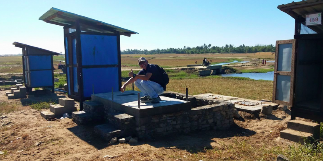 Bagus demonstrating toilet use on a partially-constructed communal TWT in Say Tha Mar Gyi camp, with a raised tank at the back of the toilet block to overcome high groundwater. Credit: Mee Mee Htun/Oxfam