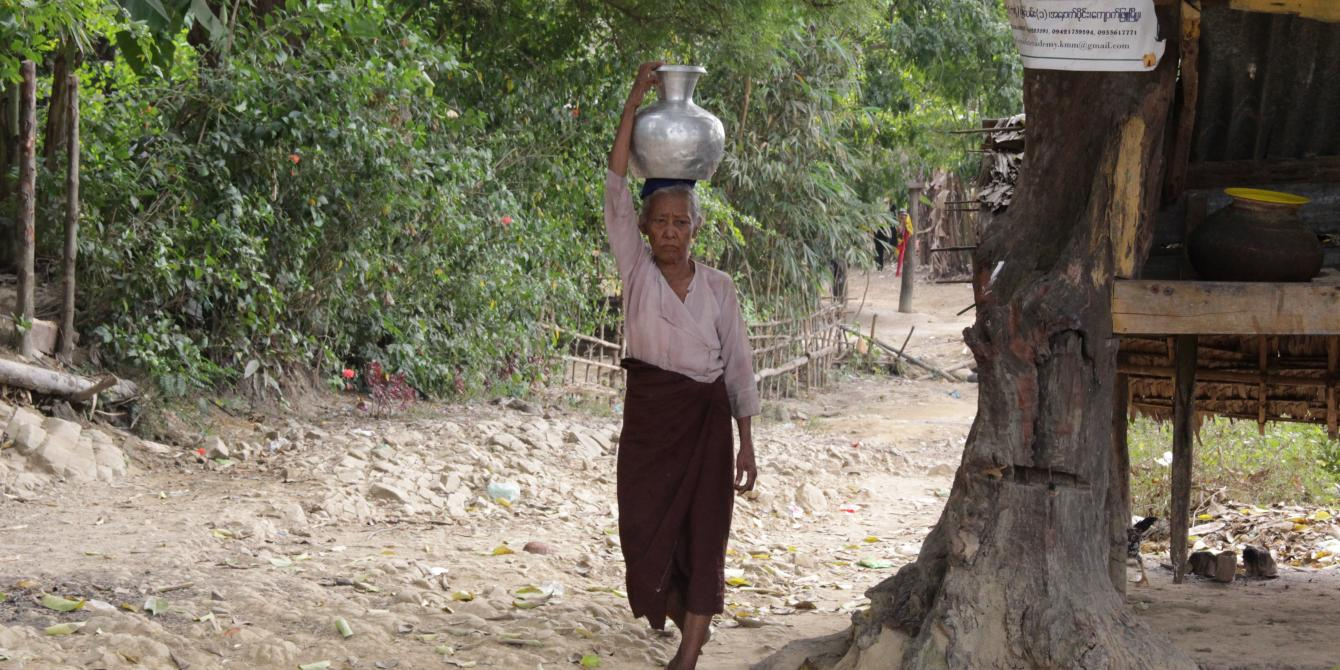 Village elderly woman carrying water on her head in Thit Pote Taung village. Photo by: Yu Lwin Soe/ Oxfam