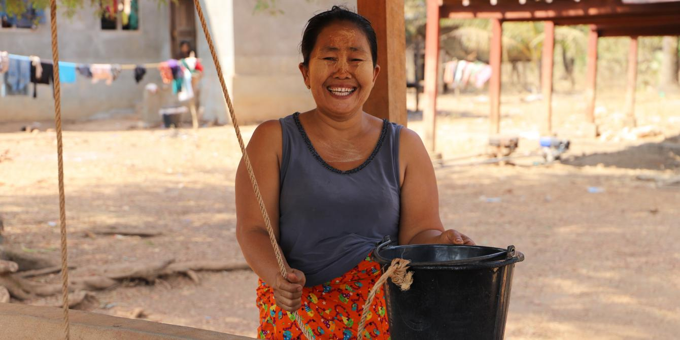 A local woman holding a water bucket near a well renovated by Oxfam/ Photo: Oxfam in Myanmar