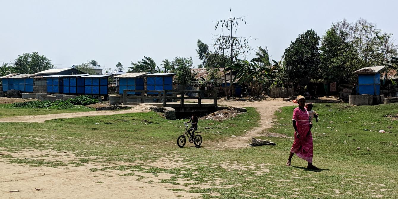 Women and children in the camps walk past latrines built by Oxfam and SolidaritesInternational