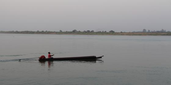 A boat carrying a woman in the river.