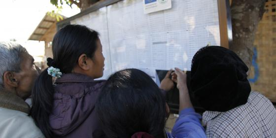 A group of people looking at distribution list on the transparency board in IDPs camp, Kachin state. Photo by: Oxfam