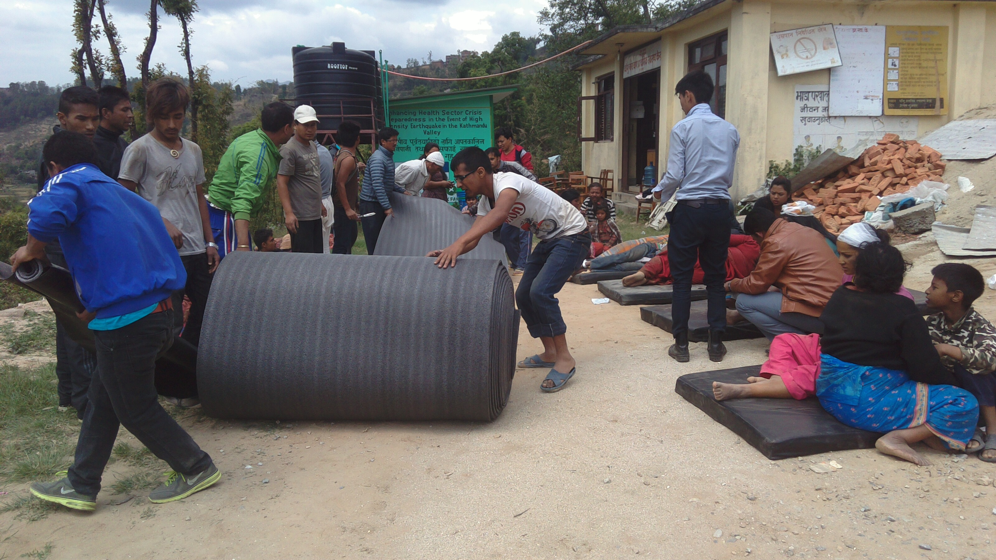 Staff trained in disaster preparedness roll out thermal mats to provide space for the treatment of many injured just an hour after the devastating earthquake - Credit: DRR Team/Oxfam