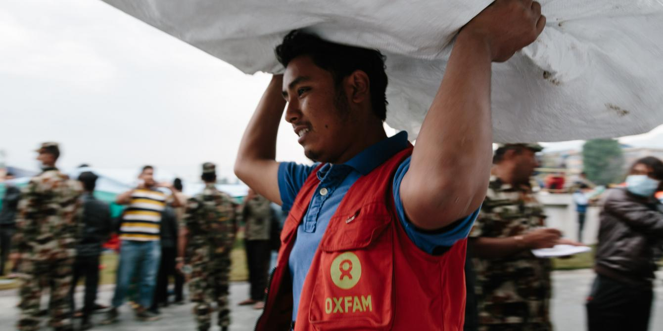 Oxfam volunteer Shekhar Khadka (23) works to off load latrines being delivered to the Tundikhel IDP camp in Kathmandu, Nepal. He is one of 500 volunteers trained to react in the event of an earthquake during the urban risk management program - Credit: Aubrey Wade/Oxfam