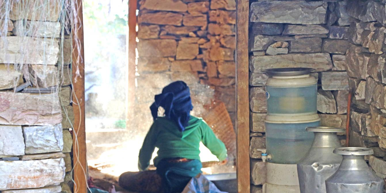A woman in Kerauja sifting grains in traditional way.
