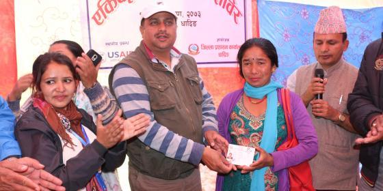 Bimala Nepali receiving citizenship certificate from Dhading's Chief District Officer, Umesh Kumar Dhakal. Photo by: Sarita Rai/Oxfam