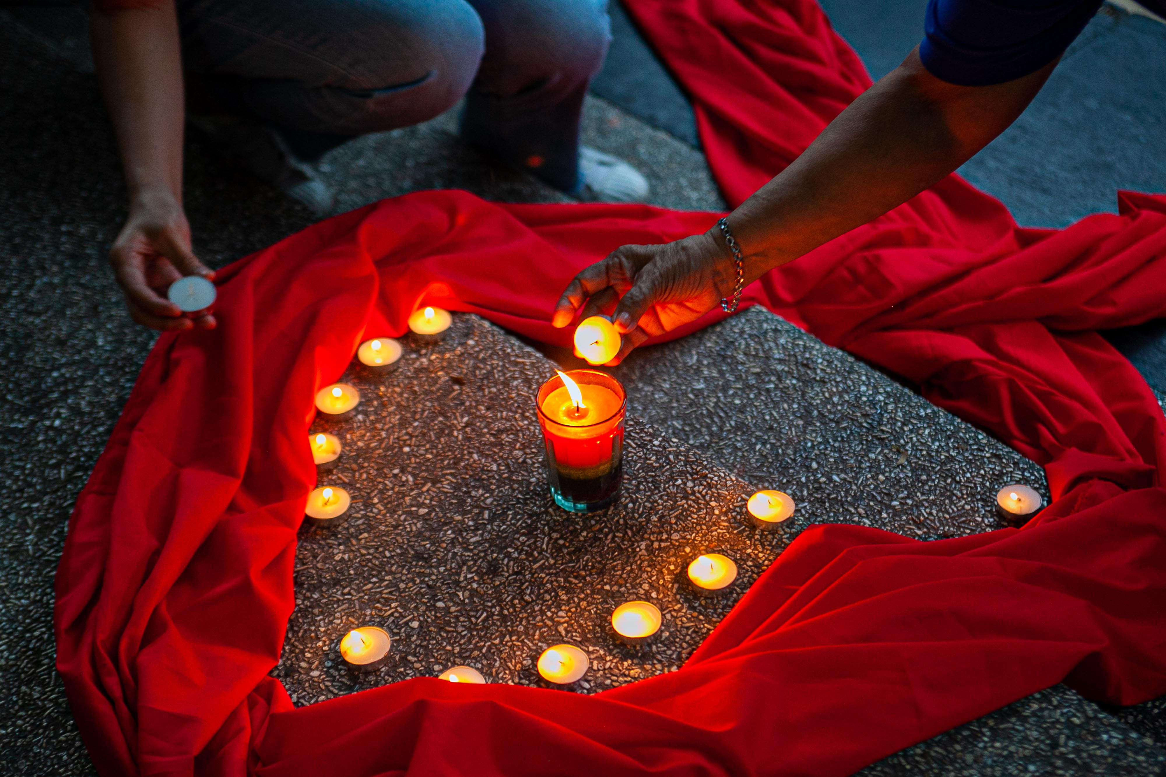 Advocates light candles during the World AIDS Day Memorial in the Philippine capital. (Photo: Mark Saludes/Oxfam)