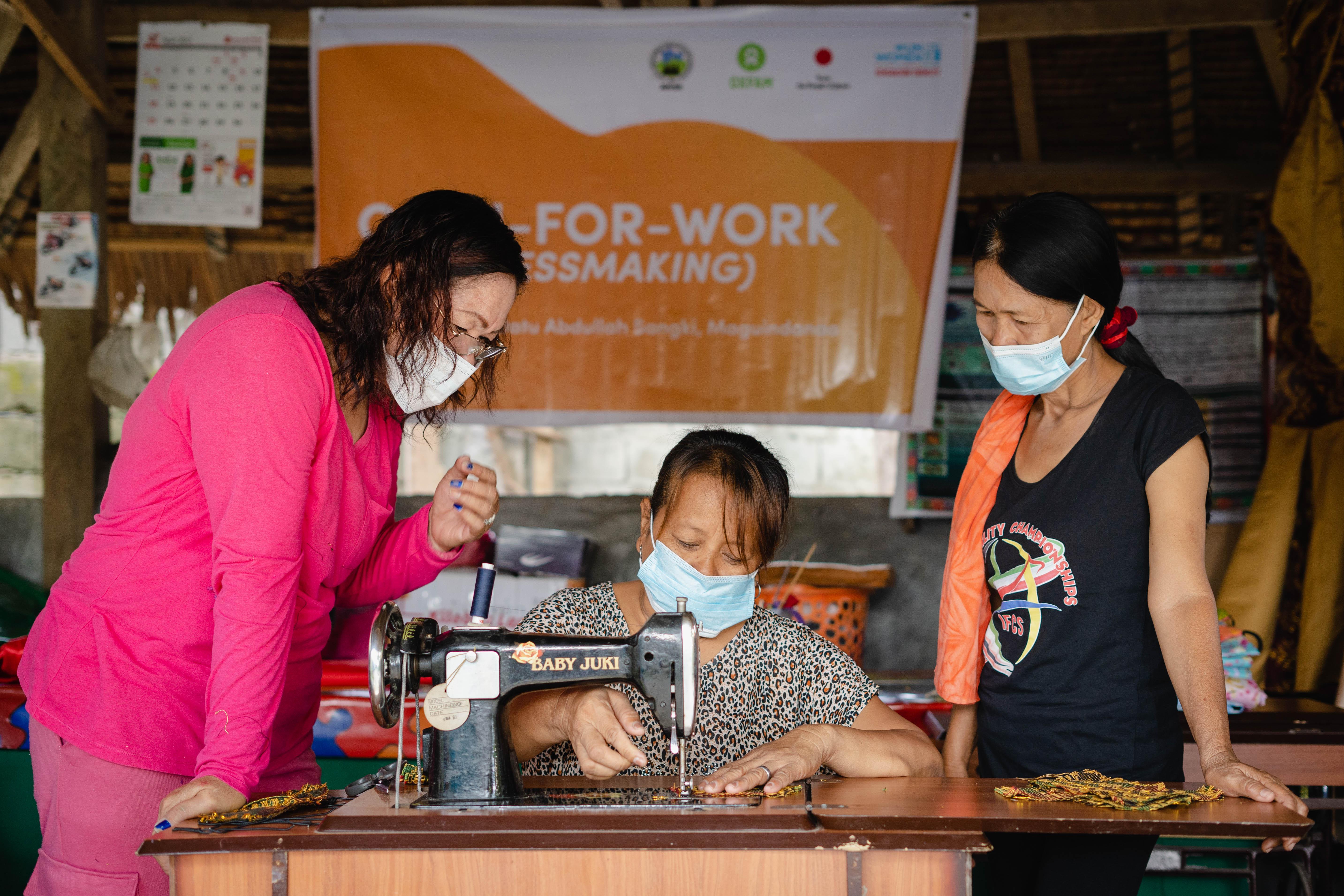 Sarah Dilangalen, Women's Federation President of Datu Abdullah Sangki, Maguindanao supervises two women on sewing Inaul face masks.