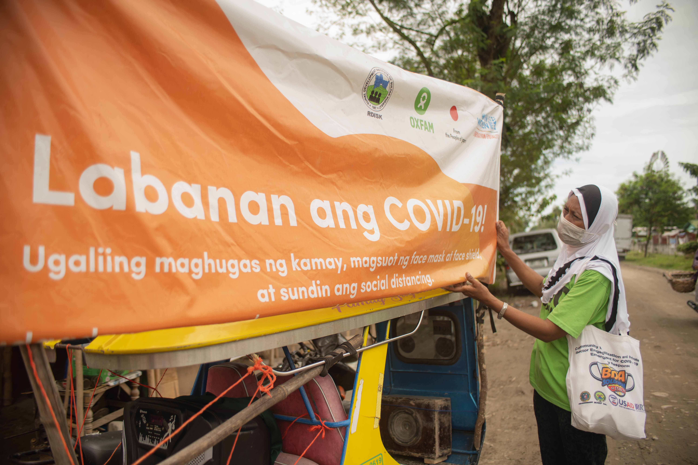 Hasna Tuwa fixes the tarp of the mobile live public announcement platform known as the rekorida before roaming around Datu Abdullah Sangki, Maguindanao. (Photo: Princess Taroza/Oxfam)