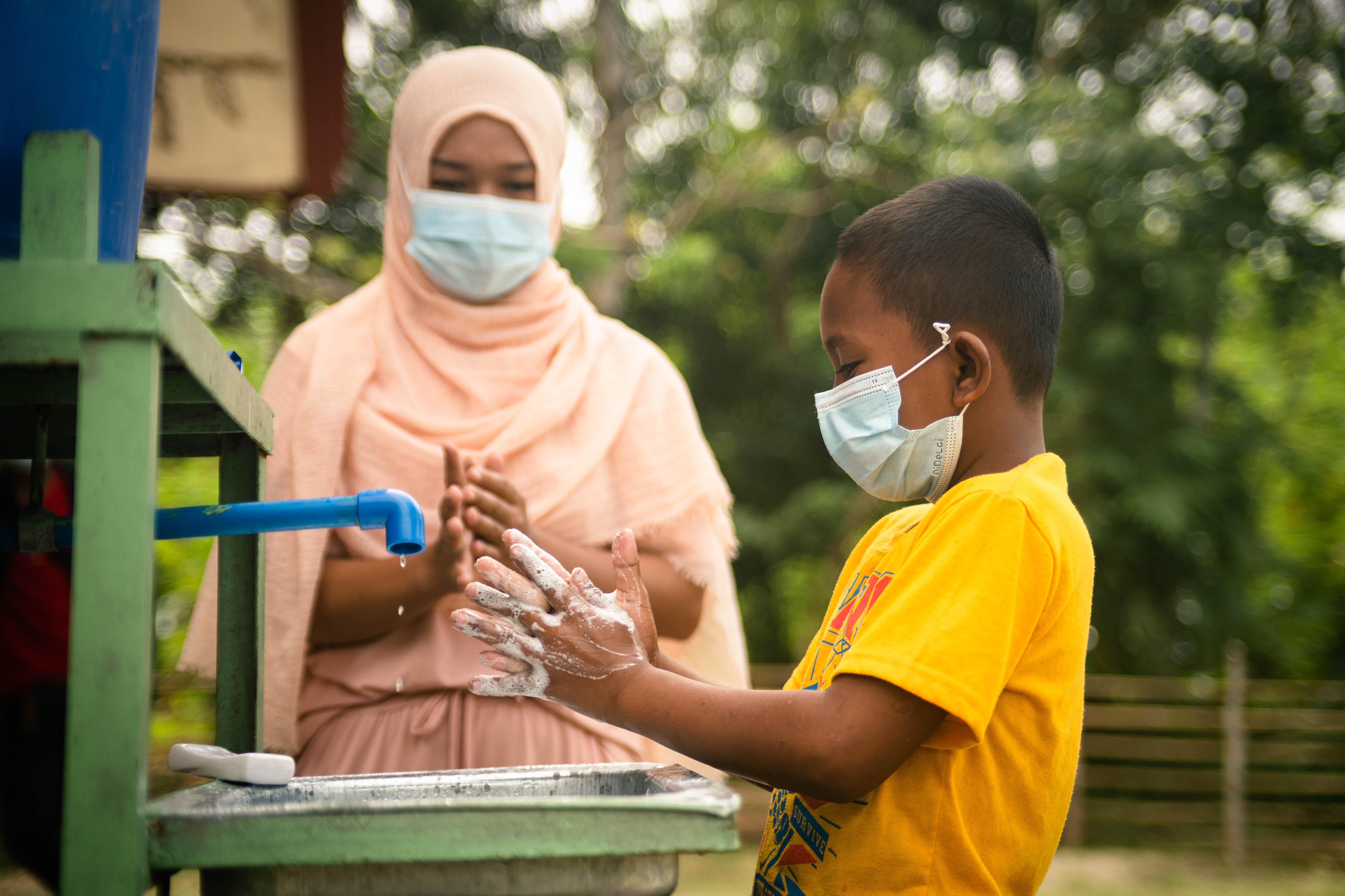Jehana Pagabangan, one of the Mum's Magic Hands (MMH) champions, teaches Mamami Piang the proper handwashing in Sultan sa Barongis, Maguindanao. (Photo: Princess Taroza/Oxfam)