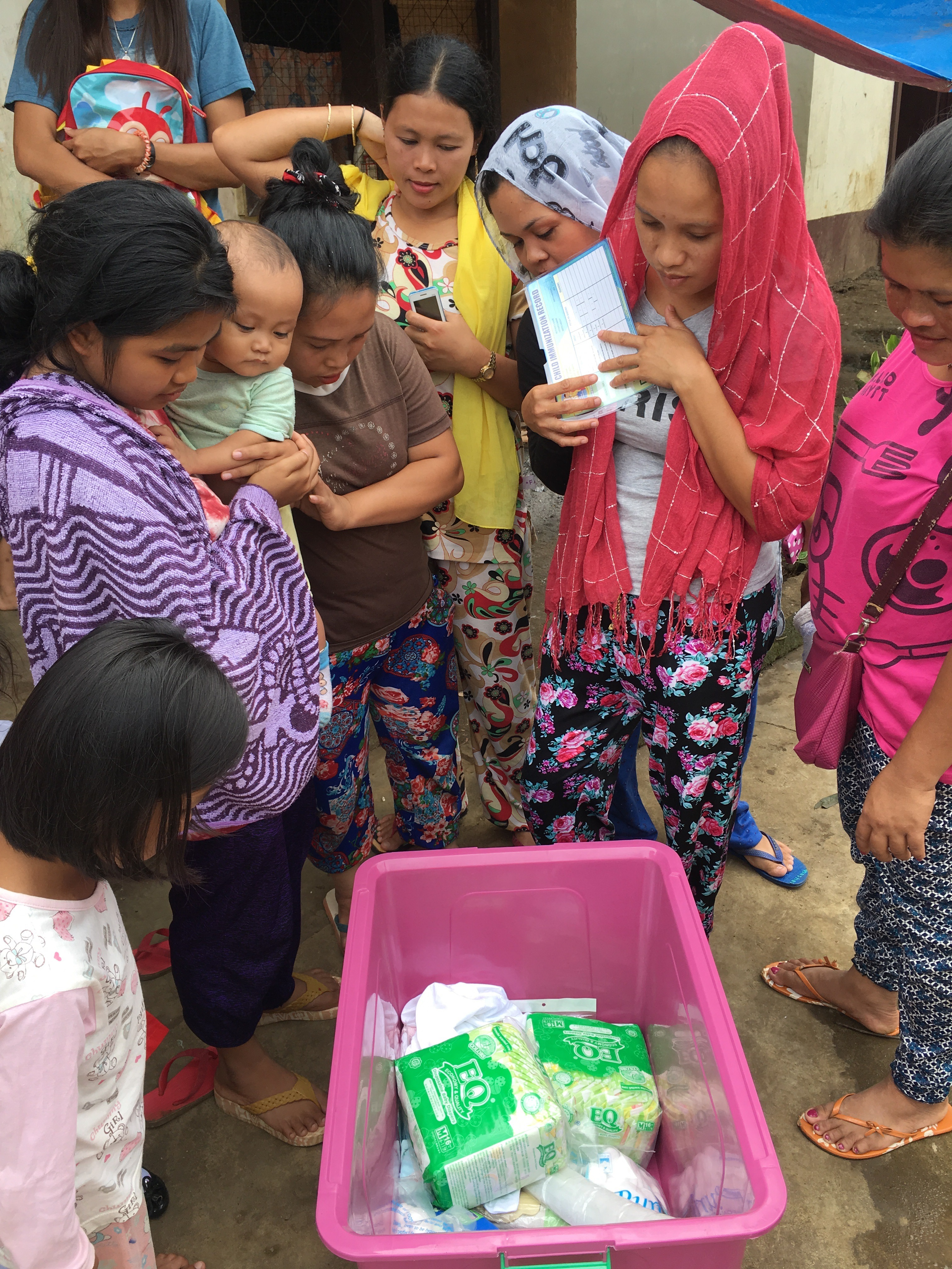 Nashreema and other women at the evacuation curious about what's inside the newborn kit