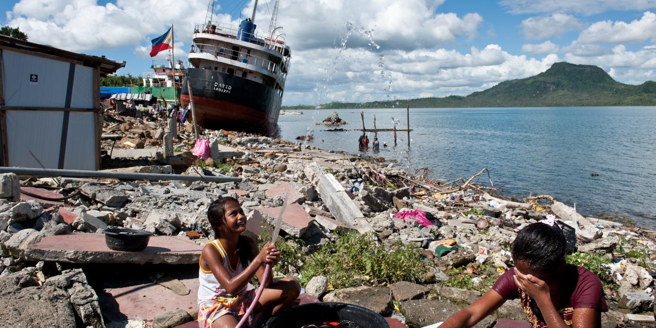 Girls wash their clothes on a stretch of coast in Tacloban where homes were flattened by the storm surge and ships crashing onto the shore. Oxfam has reached almost 550,000 people with relief in the first three months of the response, including clean water to more than 200,000 people by supporting the government to repair and fix broken pipes. (Photo: Eleanor Farmer/Oxfam)