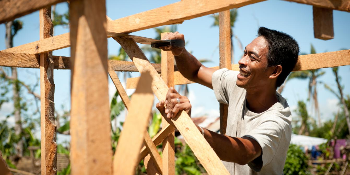 Larry Tondo (31) Carpenter and Chainsaw Operator, builds a coconut lumber sales kiosk.  (Photo: Eleanor Farmer/Oxfam)