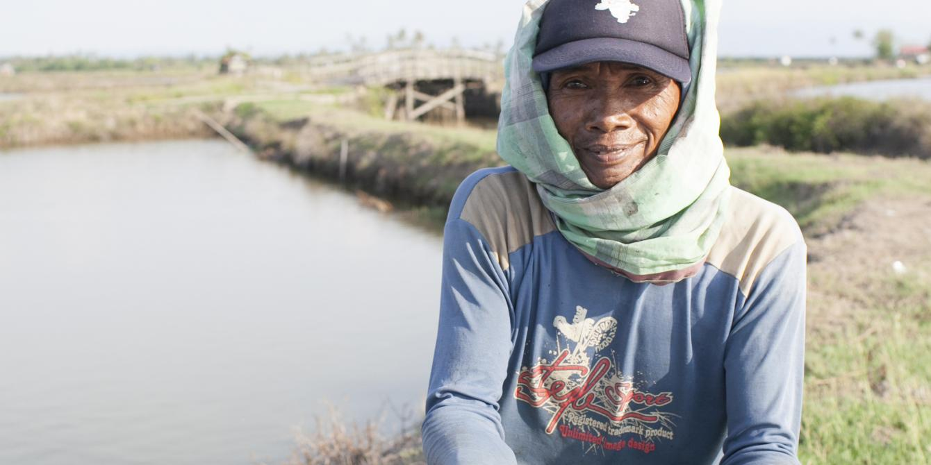 An Indonesian small-scale shrimp farmer and part of his morning harvest. One of the many farmers working alongside PT. ATINA and ASIC to create improvements in shrimp production. - Lanrisang Village, Pinrang Regency, Indonesia. (Photo by C.J. Scott)