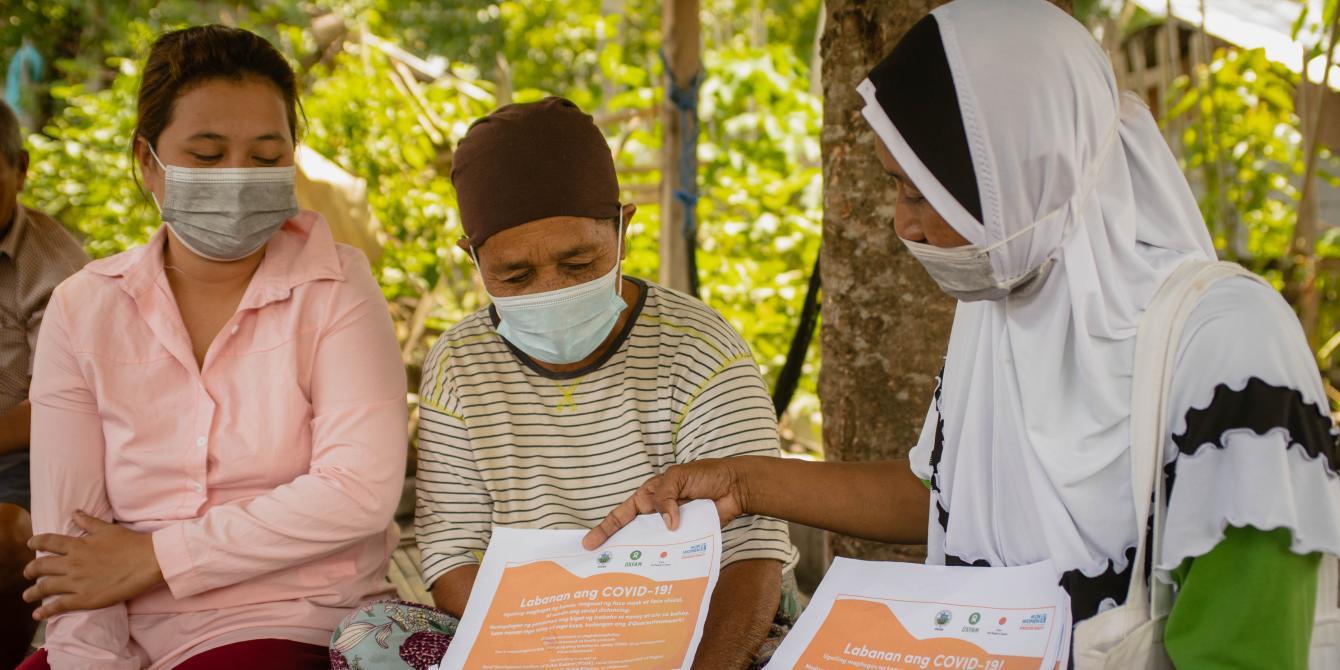 Hasna Tuwa, a local monitor and barangay health worker, explains the COVID-19 safety protocols to Datu Abdullah Sangki, Maguindanao residents. (Photo: Princess Taroza/Oxfam)