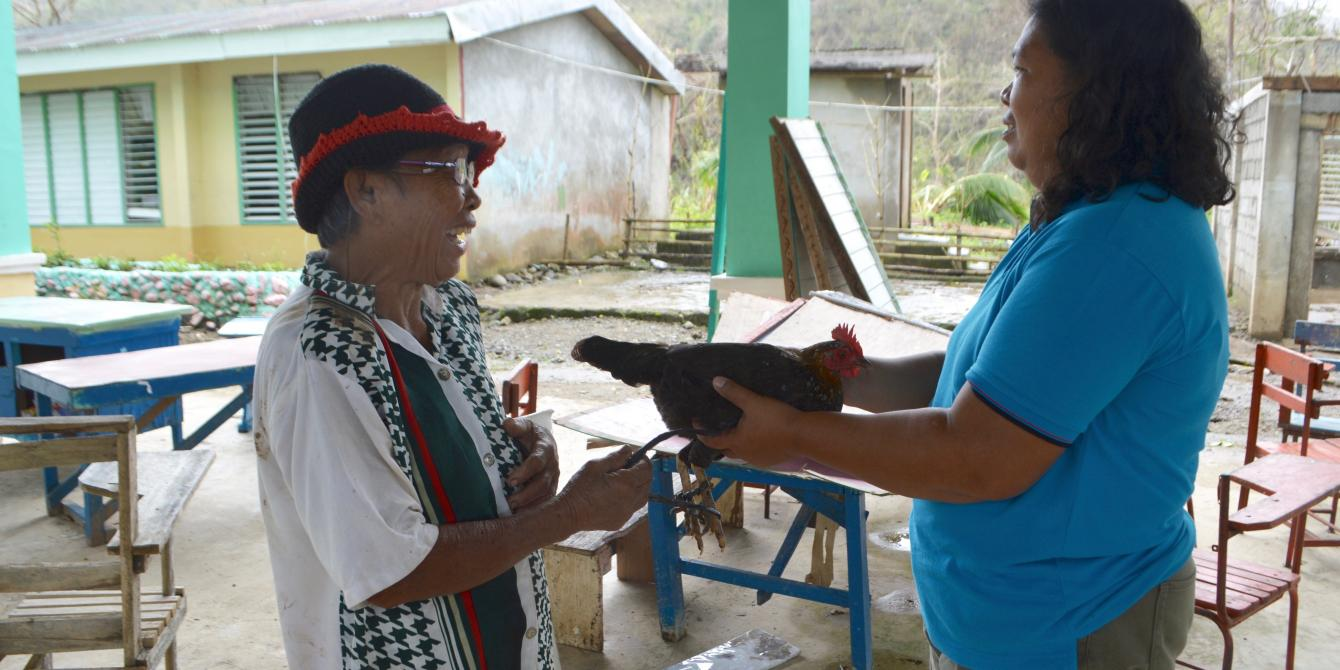 Zenita Matienco, a resident of the town gives a chicken as a token of appreciation to Rita