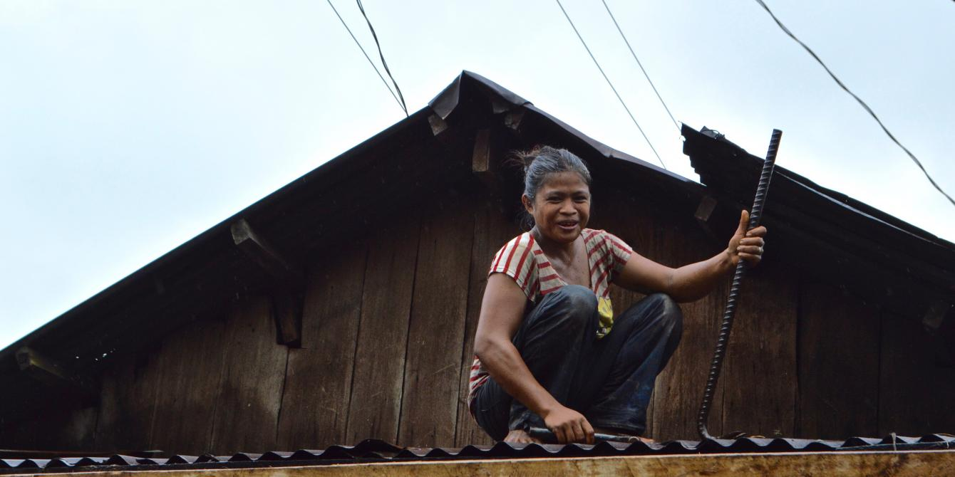 Lorena, 30, repairs the damaged roof of her house