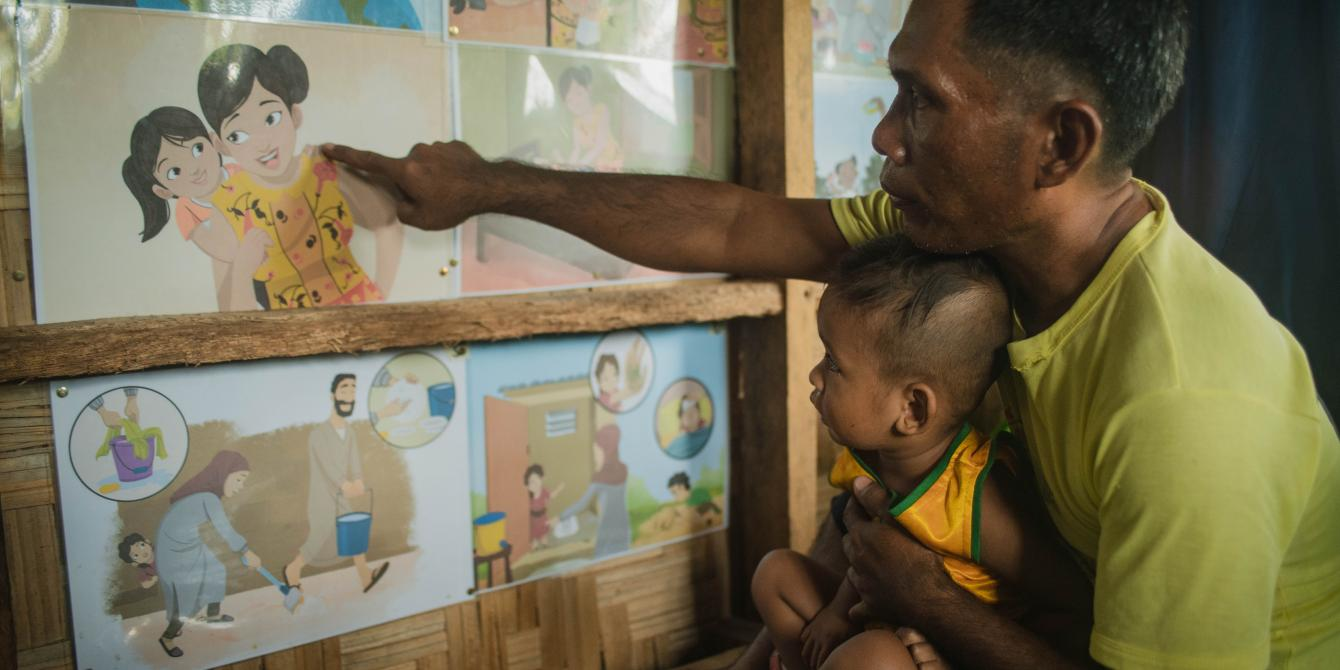Ibrahim Mantikayan, one of the MMH champions, shows the HBCC storyboards to his two-year-old son, Datu Nursalam Mantikayan, at Sultan sa Barongis, Maguindanao. (Photo: Princess Taroza/Oxfam)