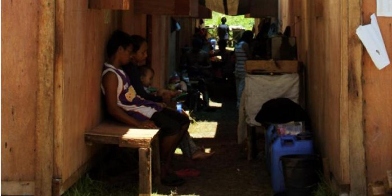 A family sits outside the bunkhouse where they continue to live after being displaced by typhoon Haiyan. Many of those in bunkhouses are being targeted for permanent resettlement to safer land as part of recovery plans. Photo: Genevive Estacaan/Oxfam 2014