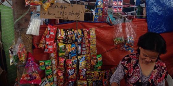 A woman sets up a small shop inside Saguiaran evacuation center