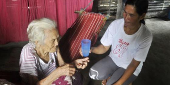 Marianita assists her 86-year-old mother in taking her medicines.