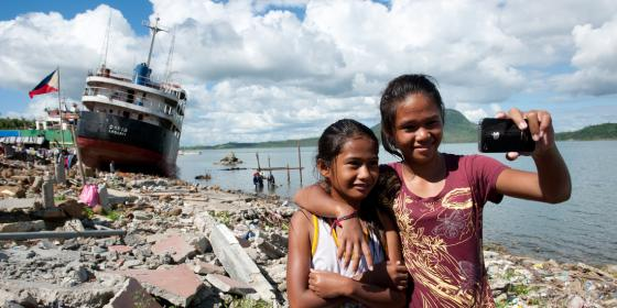 Mary Ann (10) and Mary Grace (14) stand in front of Anibong Bay in Tacloban.(Photo:Eleanor Farmer/Oxfam)