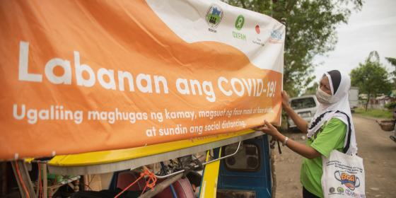 Under the scorching heat, a lady holding a megaphone with a loudspeaker beside her goes around Datu Abdullah Sangki (DAS), Maguindanao in a tricycle. The lady informs the residents of the importance of face masks, face shields, proper handwashing, and social distancing to prevent the spread of COVID-19. She also plays the rekorida, a mobile live public announcement platform, about COVID-19 safety protocols and shared unpaid care and domestic work around their community.