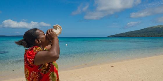 "Clerence Tamara, a leader in her island community in Vanuatu on disaster preparedness and risk reduction, blows a conch shell—a warning signal for her community. ""In my community, we blow the conch shell in emergencies, and it means 'act now!' I would like to blowthe conch shell so everyone in the world can hear it, because climate change is an emergency, and to stop it, we all need to act now."" (Photo: Elizabeth Stevens/Oxfam America)"