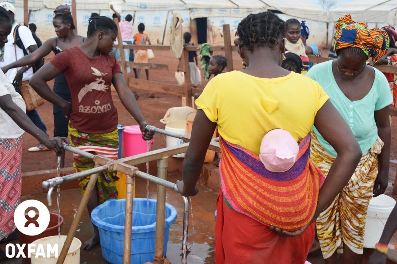 18 juillet 2019 - Des femmes viennent remplir leurs bidons à un point d'eau. Le réseau gravitaire installé par Oxfam per-met de fournir de l'eau aux 50 000 déplacés du site PK3 de Bria, dans le centre de la RCA. © Aurélie Godet/Oxfam