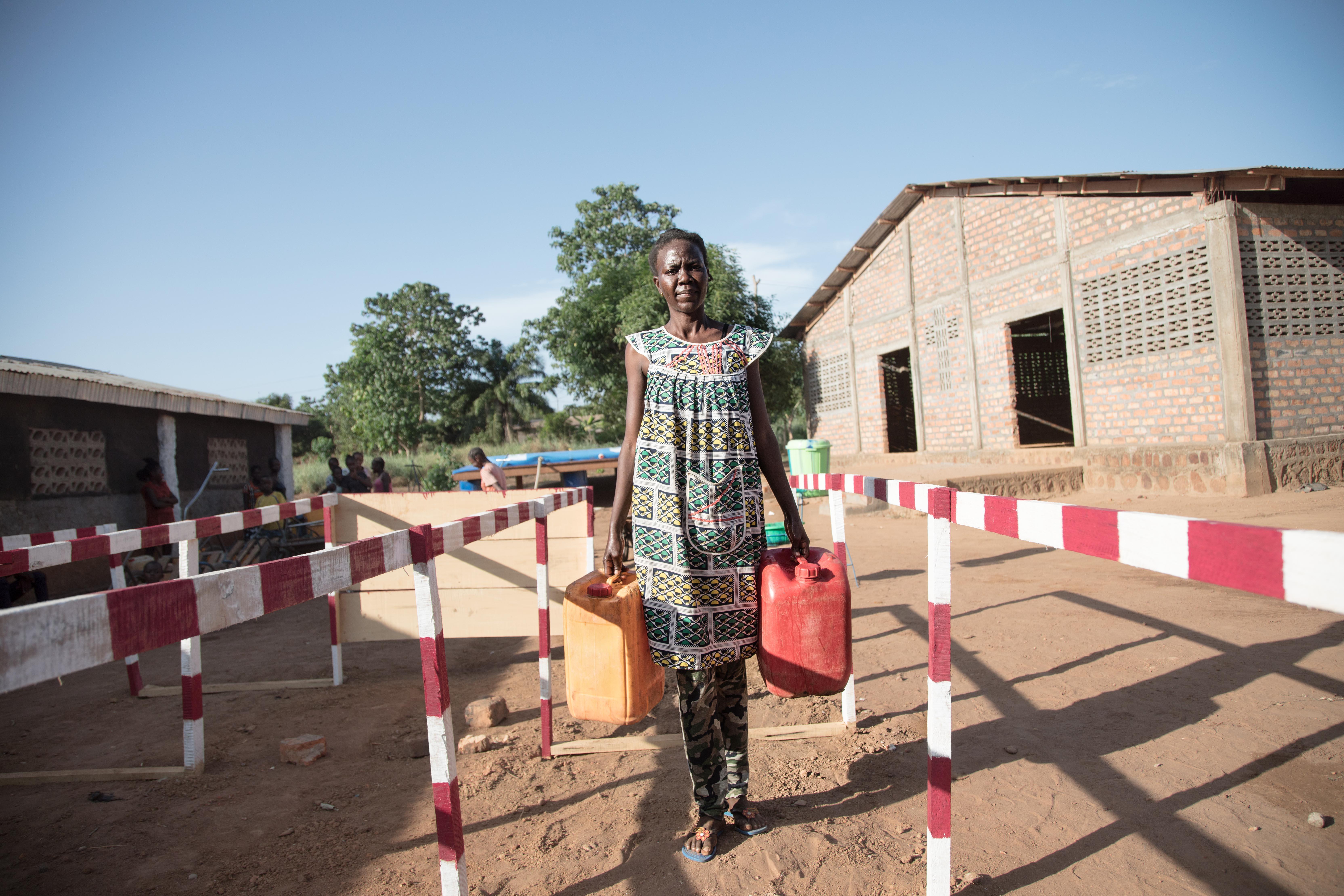 15 mai 2020 - Priscilla, 25 ans, fait la queue au point d'eau installé par Oxfam à Bimbo. Des files d'attente avec des espaces de 1 mètre sont prévues par nos équipes pour éviter la propagation du coronavirus. © Florent Vergnes/Oxfam