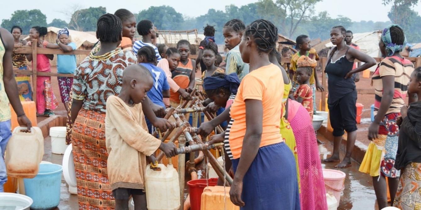 18 juillet 2019 - Des familles viennent remplir leurs bidons à un point d'eau. Le réseau gravitaire installé par Oxfam permet de fournir de l'eau aux 50 000 déplacés du site PK3 de Bria, dans le centre de la RCA. © Aurélie Godet/Oxfam